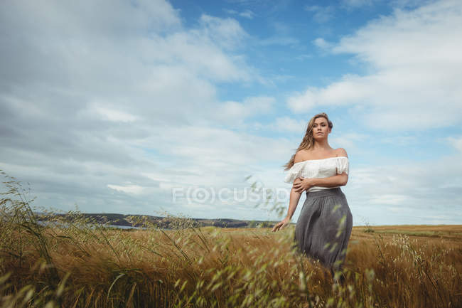 Woman standing in wheat field on sunny day in countryside — Stock Photo