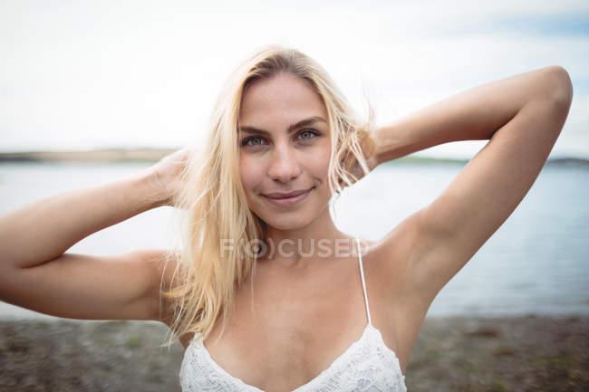 Портрет беззаботной женщины, стоящей у реки и смотрящей в камеру — стоковое фото