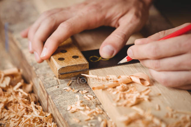 Hands of man working over a wooden plank at boatyard — Stock Photo