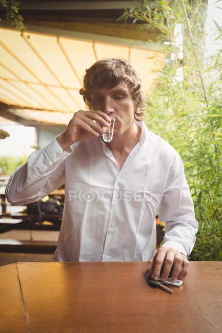 Uomo che si fa sparare di tequila al bancone del bar — Foto stock