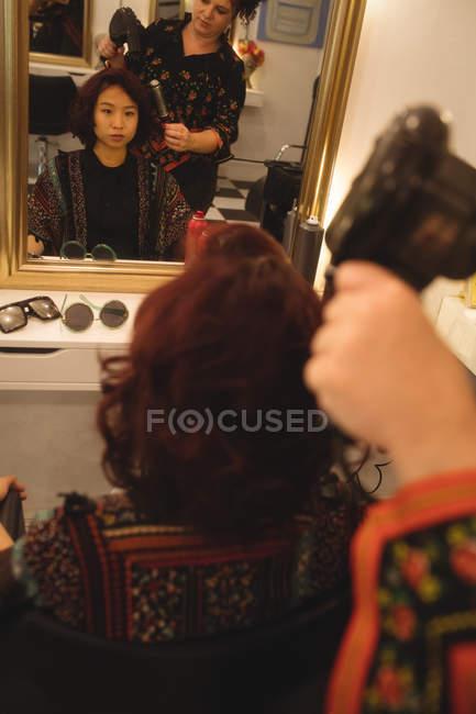 Волос стилист сушка волос клиента на профессиональный Салон — стоковое фото
