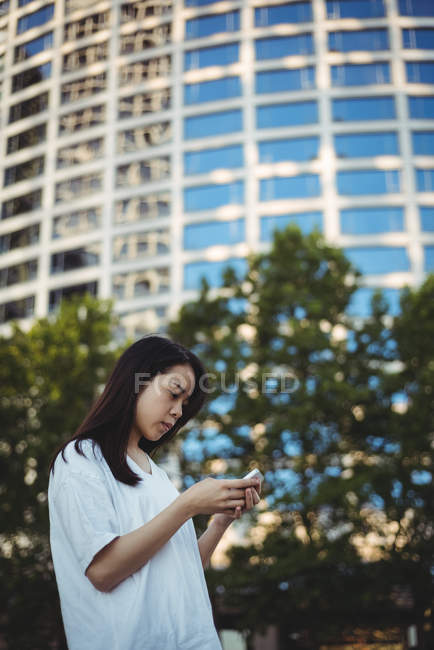 Young woman using mobile phone on street — Stock Photo