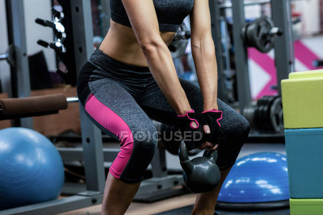 Mid-section of woman lifting kettlebell at gym — Stock Photo