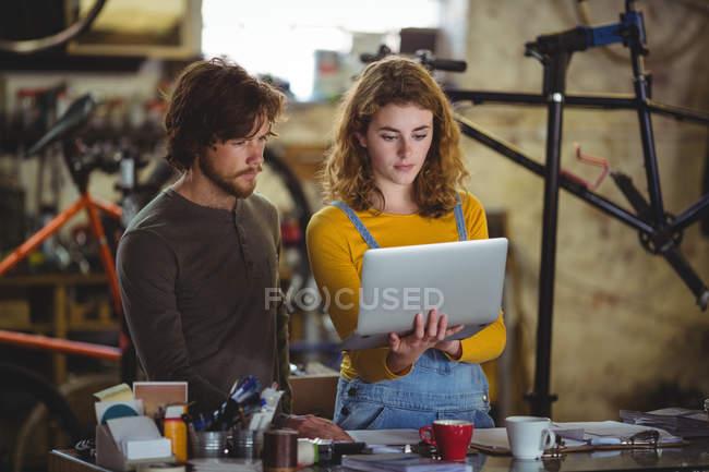 Механика использования ноутбука на прилавке в магазине велосипедов — стоковое фото
