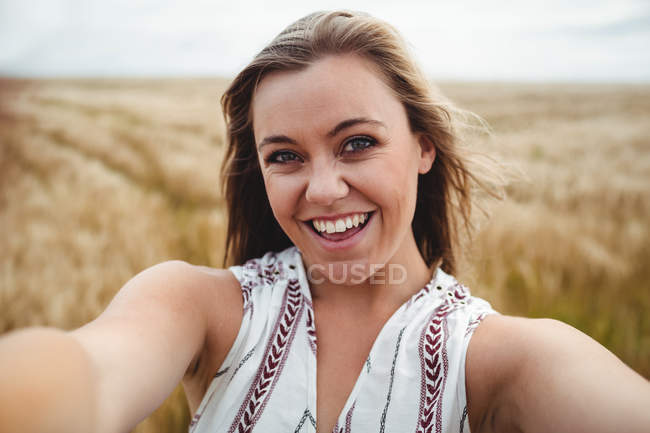 Camera point of view of smiling woman standing in wheat field on sunny day — Stock Photo