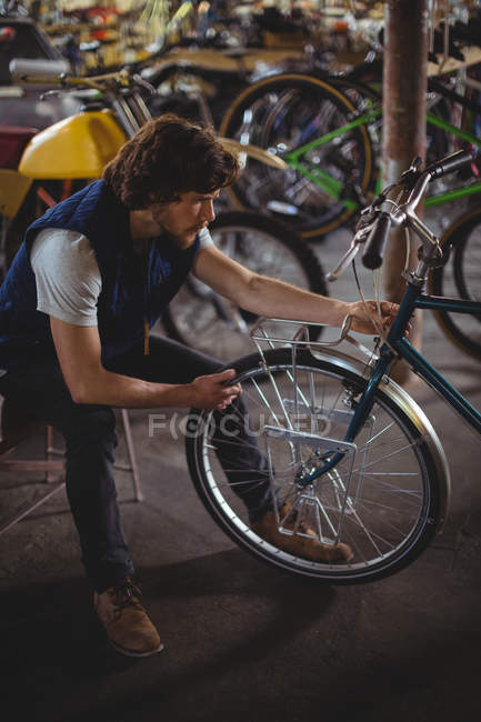 Examen de bicicleta en taller mecánico - foto de stock