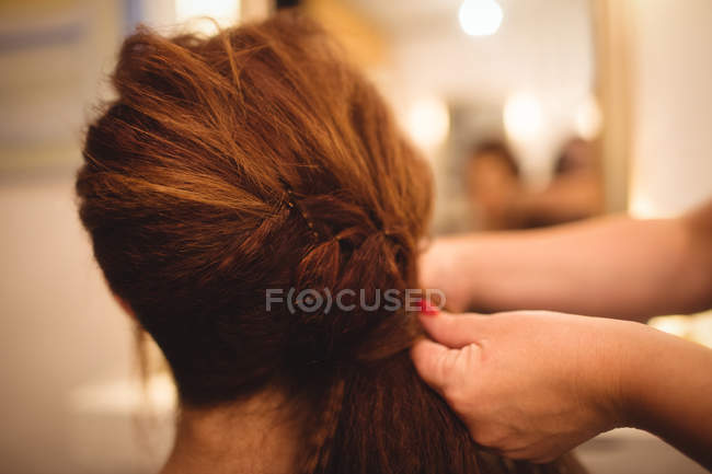 Rear view of woman styling her hair at saloon — Stock Photo