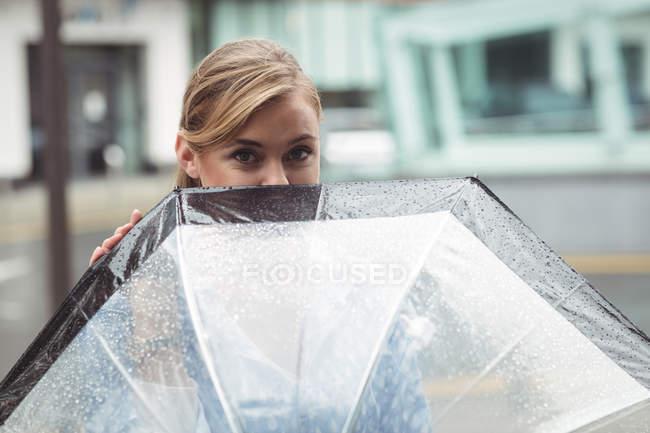 Linda mulher olhando para fora do guarda-chuva durante a estação chuvosa — Fotografia de Stock