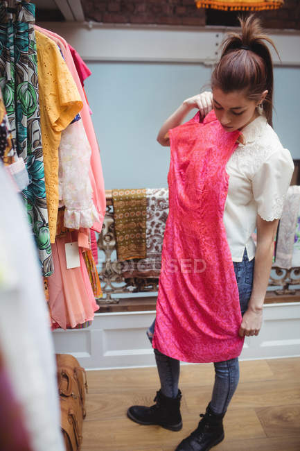 Woman selecting a clothes on hanger at apparel store — Stock Photo