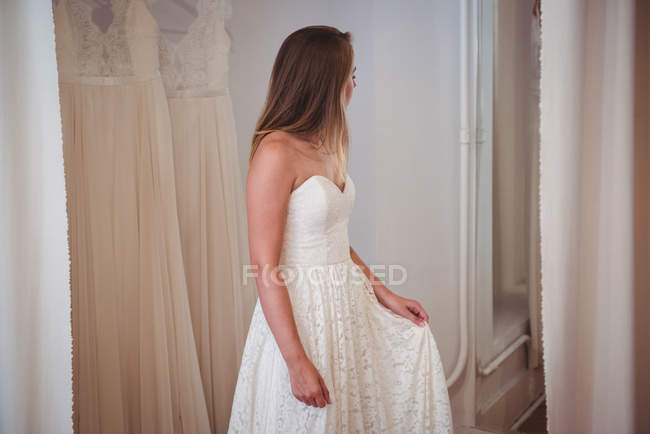 Woman trying on wedding dress in a shop in studio — Stockfoto