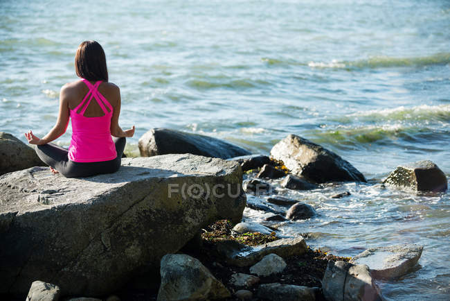 Rear view of woman sitting in lotus position with hand showing mudra gesture — Stock Photo