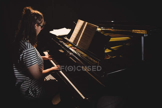Студентка играет на фортепиано в студии — стоковое фото