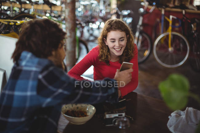 Happy couple using mobile phone in workshop — Stock Photo