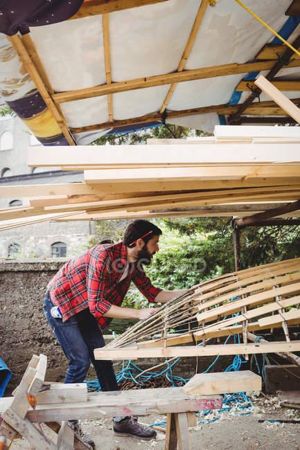 Homem preparando moldura de barco de madeira no estaleiro — Fotografia de Stock