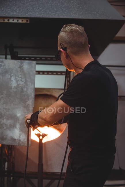 Verre chauffant de souffleur de verre dans le four à l'usine de soufflage de verre — Photo de stock