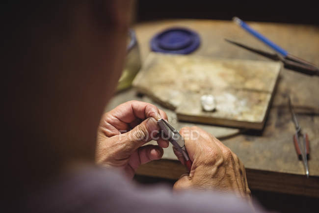 Close-up of craftswoman using pliers in workshop — Stock Photo