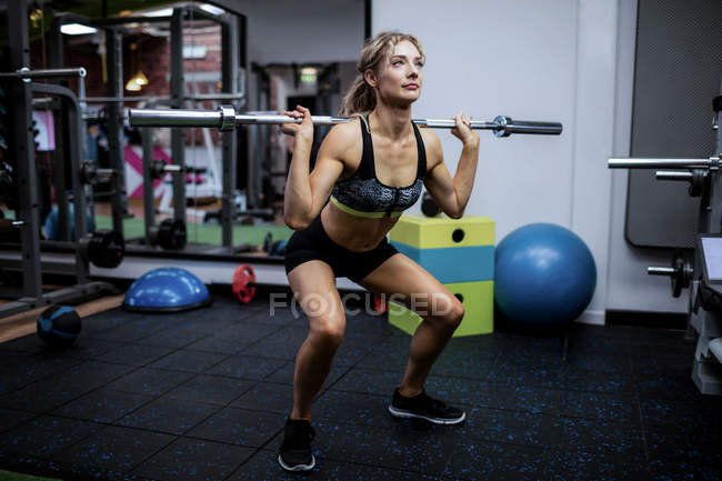 Beautiful woman working out with barbell at gym — Stock Photo