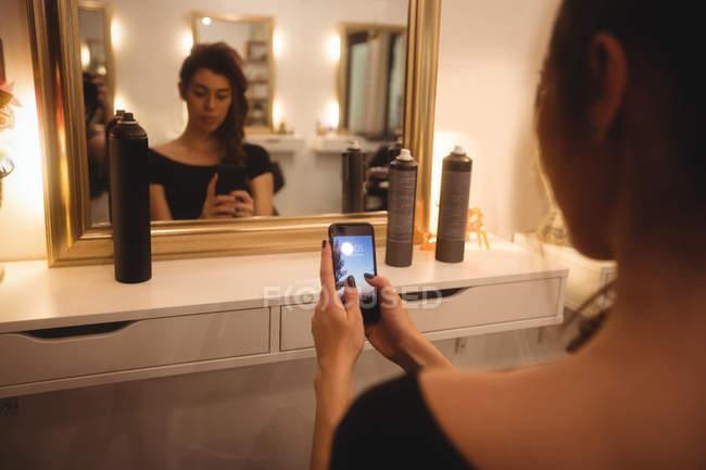 Женщина с помощью мобильного телефона в салон красоты — стоковое фото