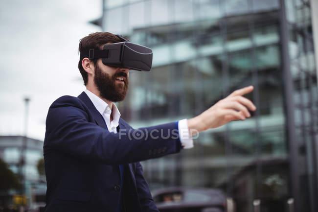 Бізнесмен, використовуючи гарнітуру віртуальної реальності за межами офісу — стокове фото
