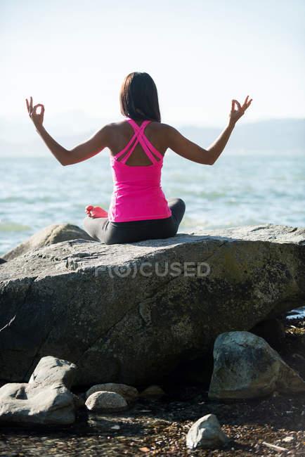 Rückansicht des Frau Yoga auf Felsen auf der sonnigen Tag und zeigen Mudra-Geste — Stockfoto