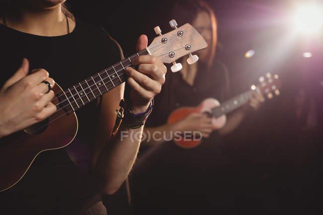 Women playing a guitar in music school — Stock Photo