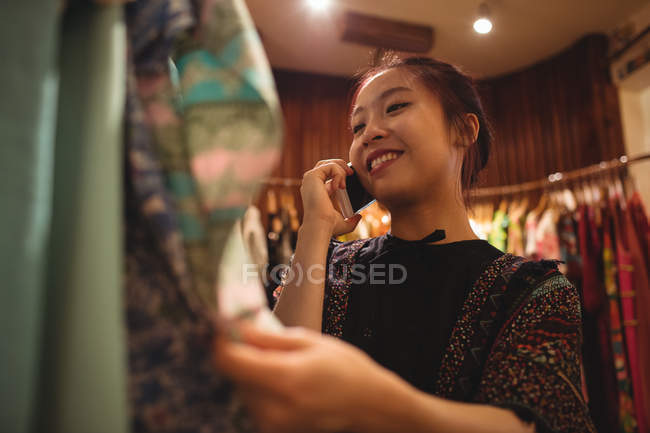 Woman talking on mobile phone while selecting clothes on hangers at apparel store — Stock Photo