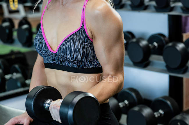 Mid-section of woman lifting dumbbells at gym — Stock Photo