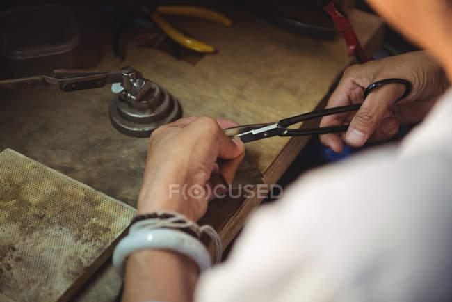 Hands of craftswoman using scissors in workshop — Stock Photo