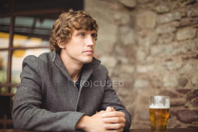 Вдумчивый человек сидит в баре со стаканом пива на столе — стоковое фото