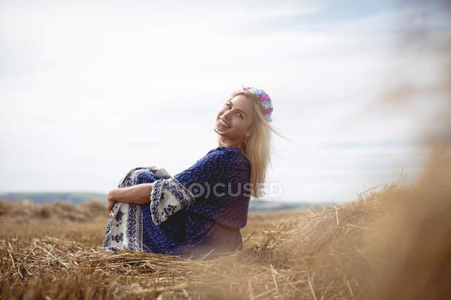 Улыбающаяся блондинка, сидящая в поле и смотрящая в камеру — стоковое фото