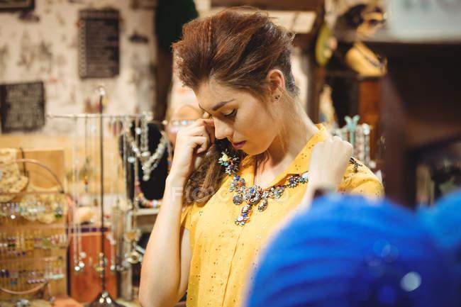 Женщина в винтажном ожерелье в антикварном магазине — стоковое фото