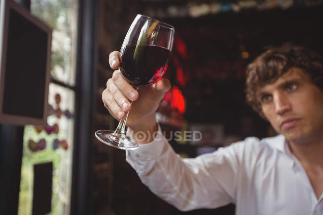 Bartender looking at glass of red wine at bar counter — Stock Photo