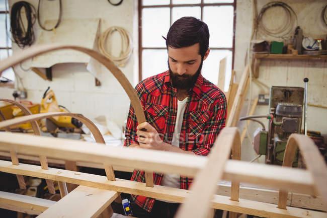 Mann bereitet auf Bootswerft einen Holzrahmen vor — Stockfoto