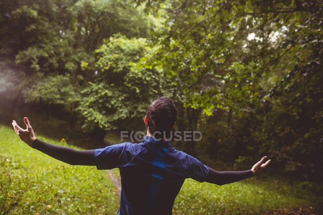 Atleta emozionato con le braccia protese in foresta — Foto stock
