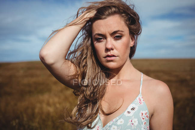 Portrait of woman with hand in hair standing in wheat field on sunny day — Stock Photo