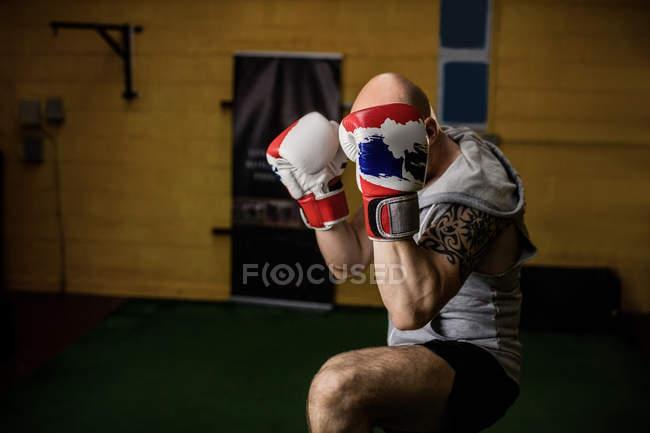 Татуированный тайский боксер, занимающийся боксом в спортзале — стоковое фото