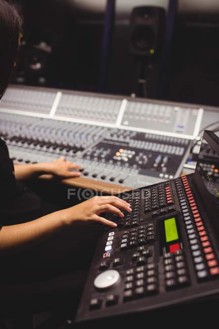 Студентка, использующая звуковую микшерную клавиатуру в студии — стоковое фото