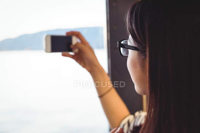 Nahaufnahme einer Frau, die vom Schiff aus mit dem Handy fotografiert — Stockfoto