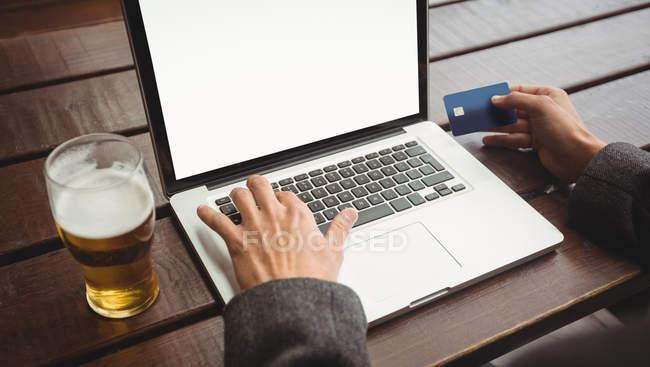 Uomo che fa shopping online con carta di credito sul computer portatile nel bar — Foto stock