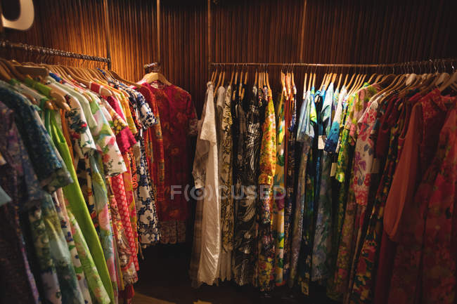 Female clothes arrangement on hangers in vintage boutique — Stock Photo