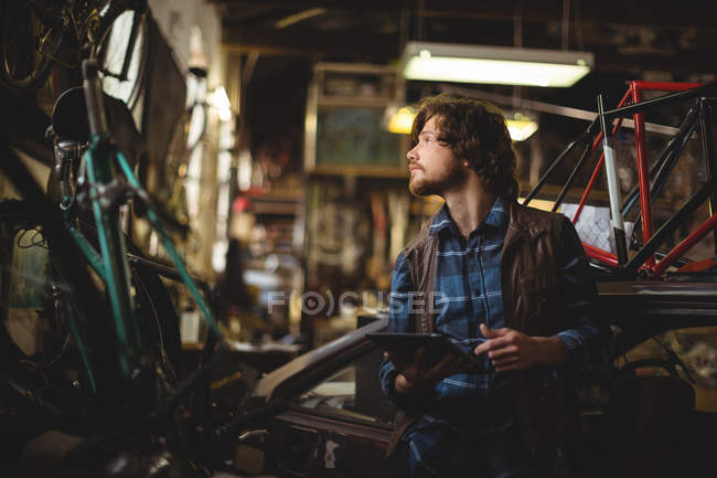 Mechanic using digital tablet while repairing bicycle in workshop — Stock Photo