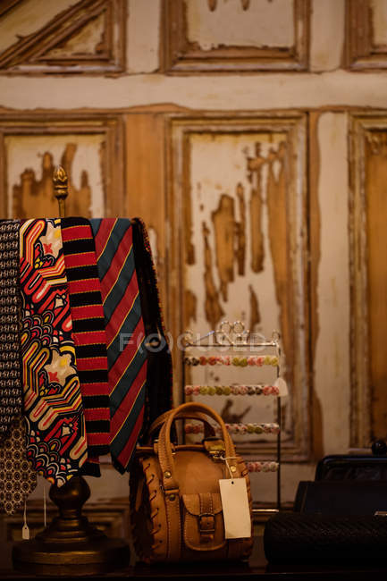 Various ties and handbag on display in boutique store — Stock Photo