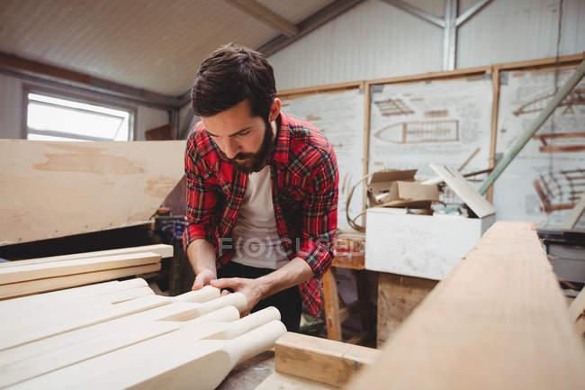 Man working on wooden plank in boatyard — Stock Photo