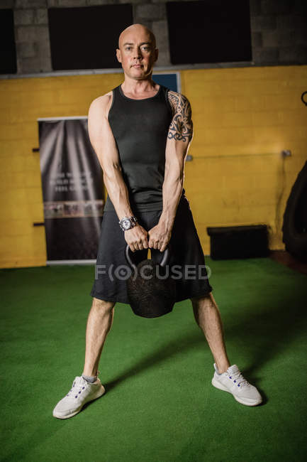 Красивий спортсмен підйому ваги в тренажерному залі і, дивлячись на камеру — стокове фото