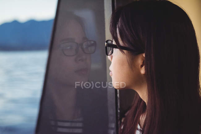 Продуманий молода жінка дивлячись через вікно під час вашого перебування в корабель — стокове фото