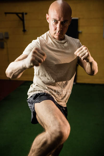 Boxer sérieux pratiquant la boxe dans un studio de fitness — Photo de stock