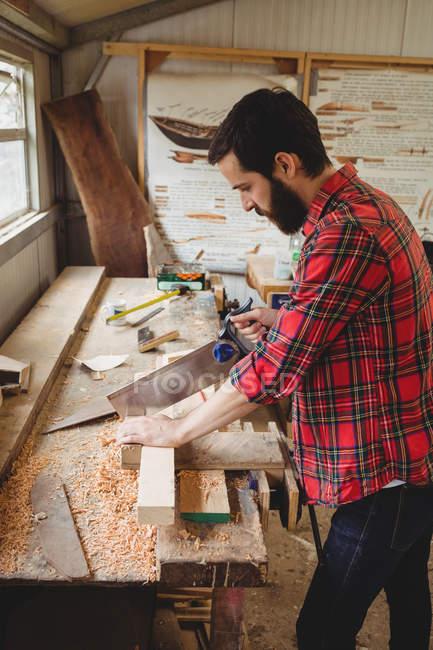 Человек режет деревянную доску на лодочной станции — стоковое фото