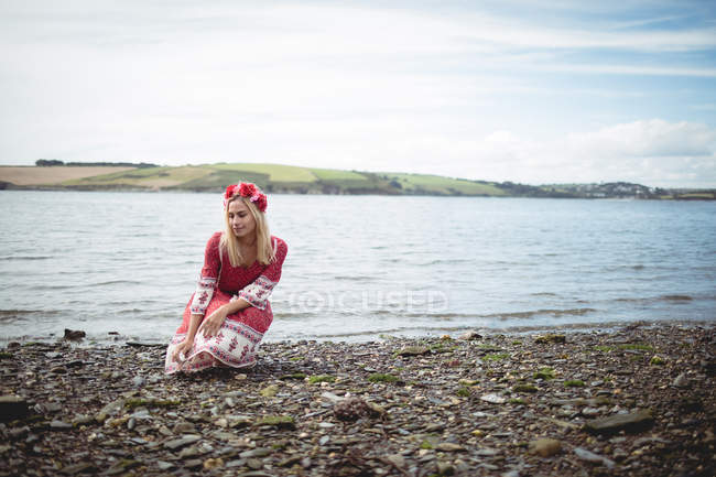 Carefree blonde woman in red dress and flower tiara sitting near river — Stock Photo