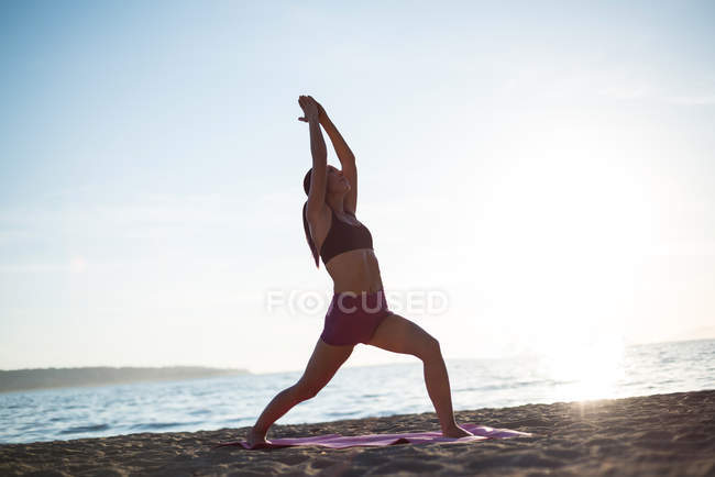 Low angle view of Woman performing yoga on beach on sunny day — Stock Photo