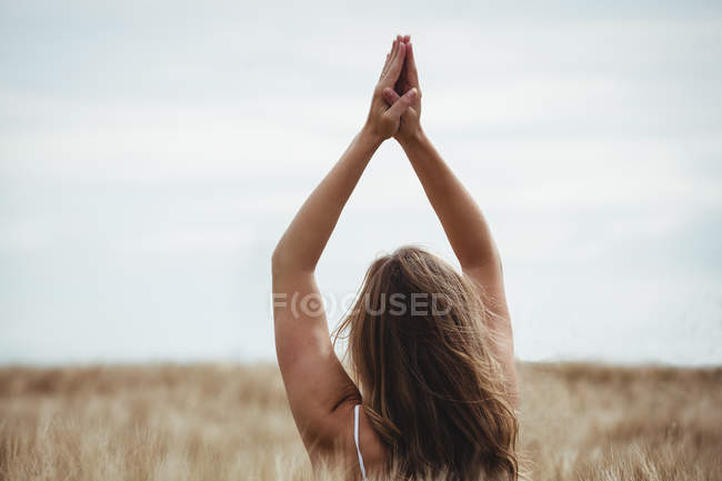 Woman with hands raised over head in prayer position in field on a sunny day — Stock Photo